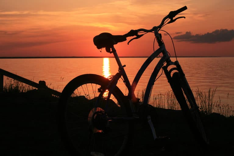 Bicycle with sunset across the lake in the background.