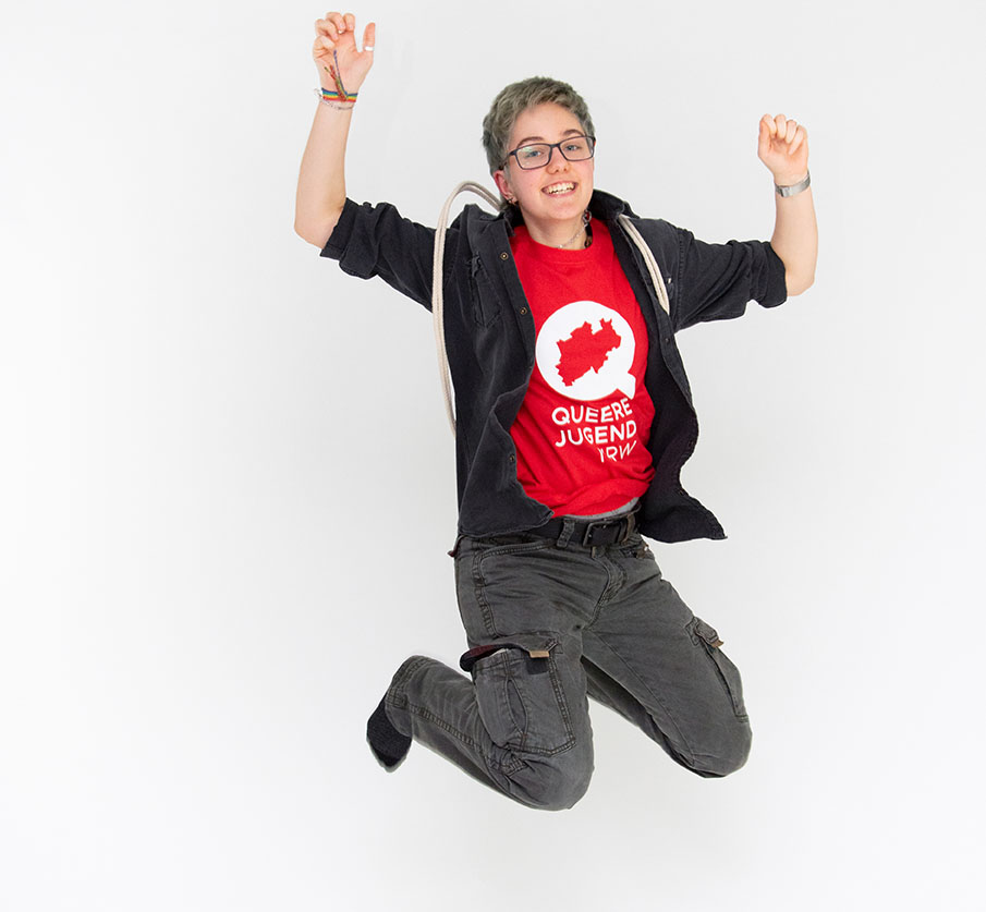 """Bild Oben: Das Bild zeigt Person die in die Luft springt und lächelt. Die Person trägt ein rotes T-Shirt mit dem Logo der Queeren Jugend NRW dieses besteht aus einem Weißen """"Q"""" mit einer Ausstanzung in Form von NRW in der Mitte und dem Schriftzug """"Queere Jugend NRW"""""""