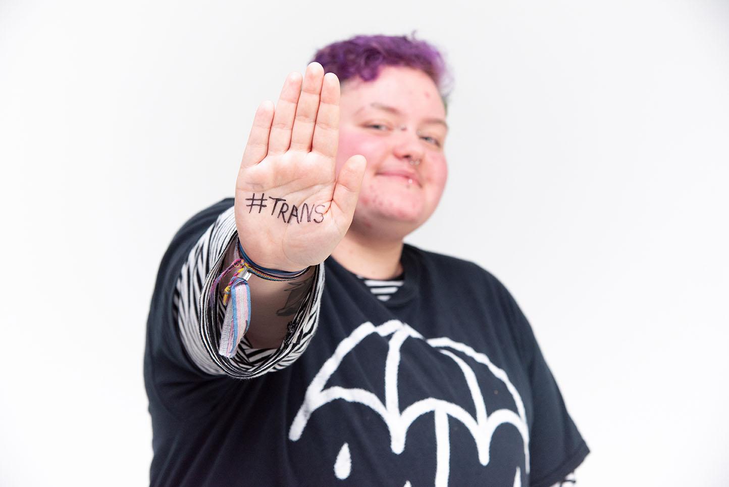 """Das Bild zeigt eine Person die auf der Handfläche """"#trans"""" stehen hat und diese Richtung Kamera zeigt."""
