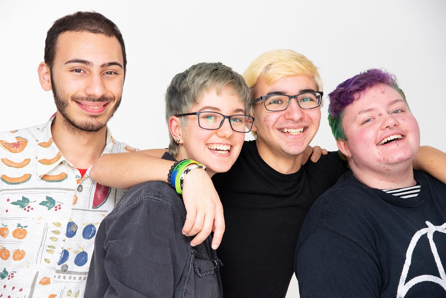 Das Bild zeigt vier Personen die die Arme um einander legen eine Person hat grün-lila gefärbte Haare.