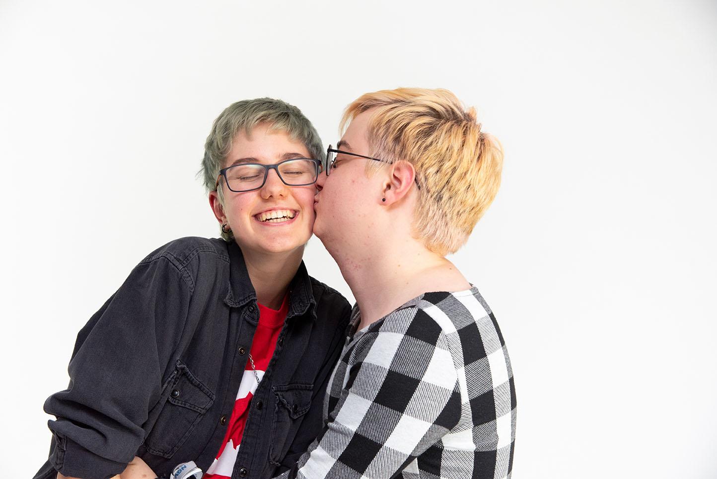 Das Bild zeigt Zwei Personen die eine Person gibt der anderen einen Kuss auf die Wange.