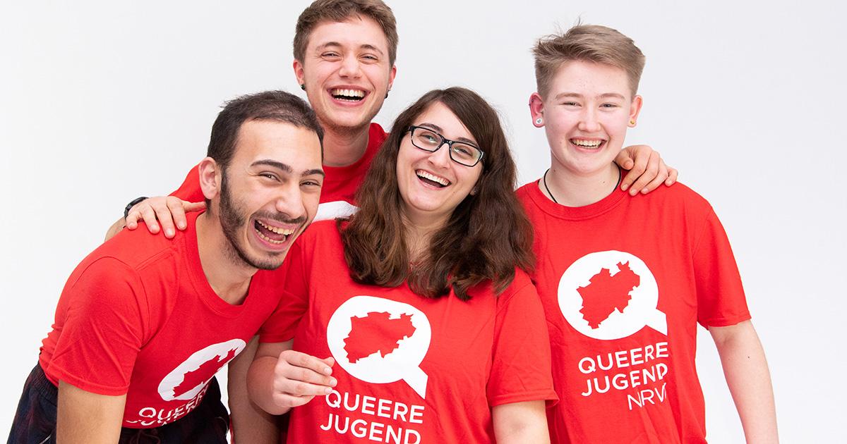 """Das Bild zeigt vier Personen die herzhaft lachen. Drei der Personen haben kurze Haare eine Person hat lange Haare. Alle Vier trage Rote T-Shirts mit dem Logo der Queeren Jugend NRW dieses besteht aus einem Weißen """"Q"""" mit einer Ausstanzung in Form von NRW in der Mitte und dem Schriftzug """"Queere Jugend NRW"""""""