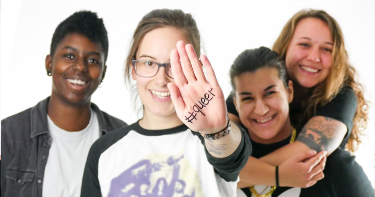 """Das Bild zeigt Vier Personen, eine Person zeigt ihre Handfläche in Richtung der Kamera auf der Handfläche steht """"#queer""""."""