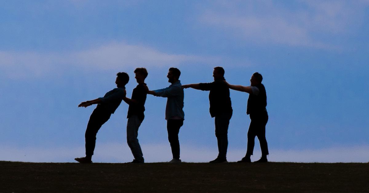 Das Bild wurde im halb-dunkeln aufgenommen es zeigt fünf Personen die in einer Reihe hinter einander stehen und sich gegenseitig stützen.