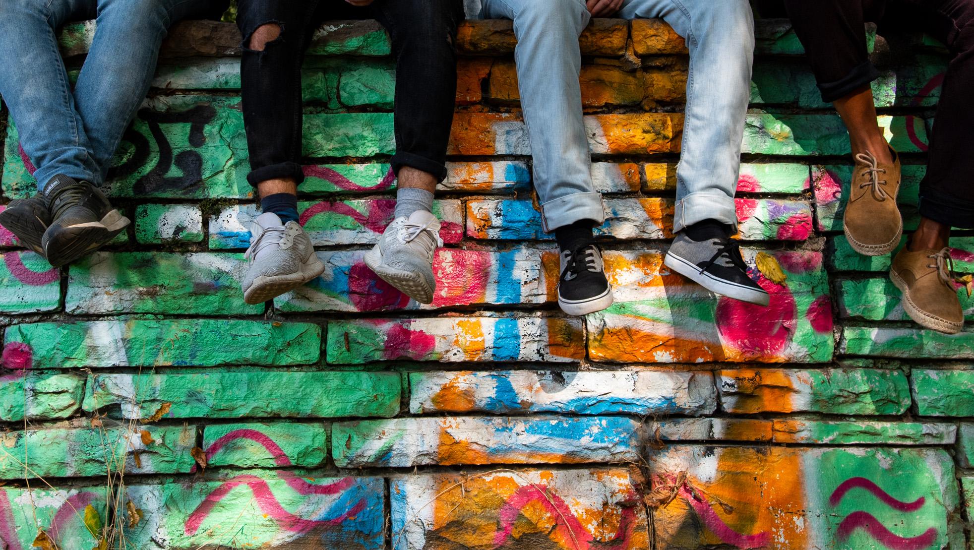 Das Bild zeigt eine bunt bemalte Steinwand, man sieht vier Paar Beine von Personen die auf der Mauer sitzen.