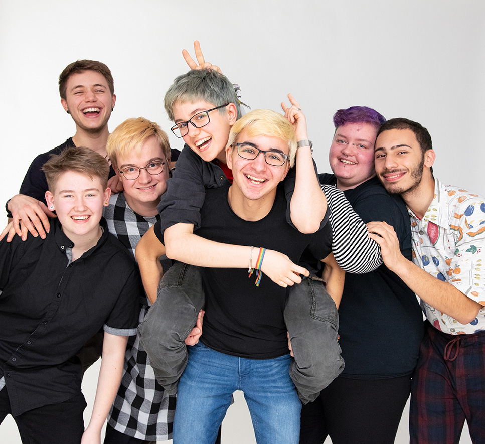 Das Bild zeigt Sieben lächelnde Personen die zusammen für das Photo posieren. Eine Person wird von einer anderen Huckepack genommen. Der Hintergrund ist komplett weiß.