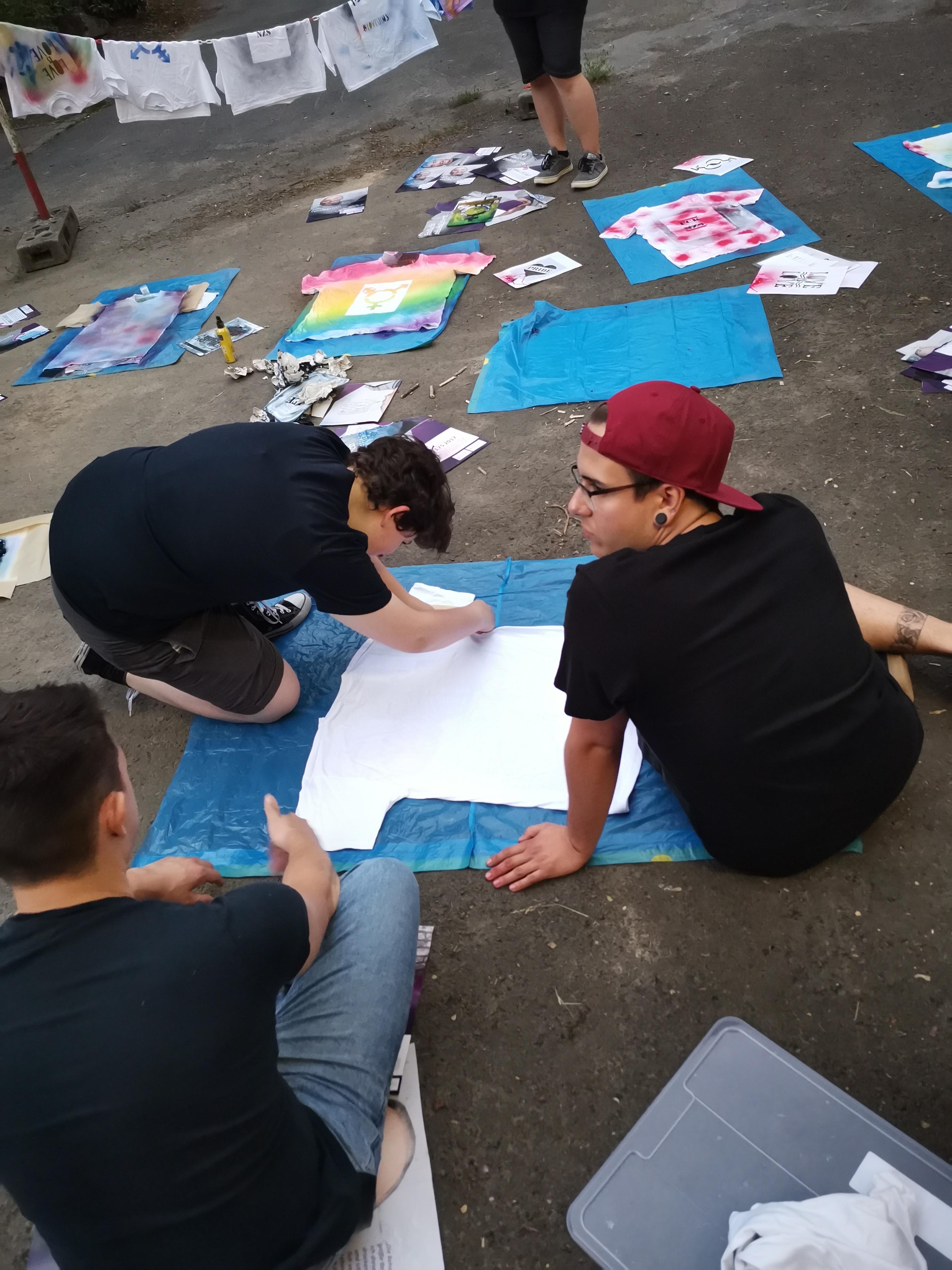 Das Bild zeigt Menschen bei Plakate bemalen