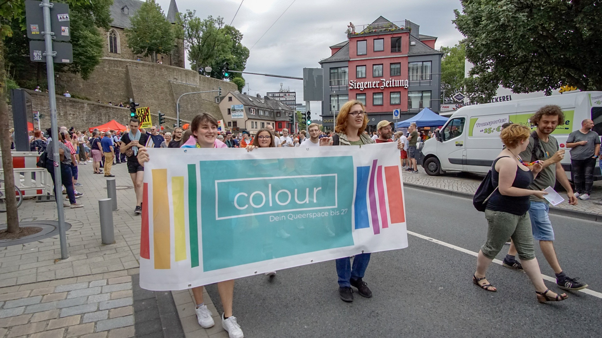 Das Bild zeigt Menschen bei der CSD Demo mit einem Banner von Colour Siegen