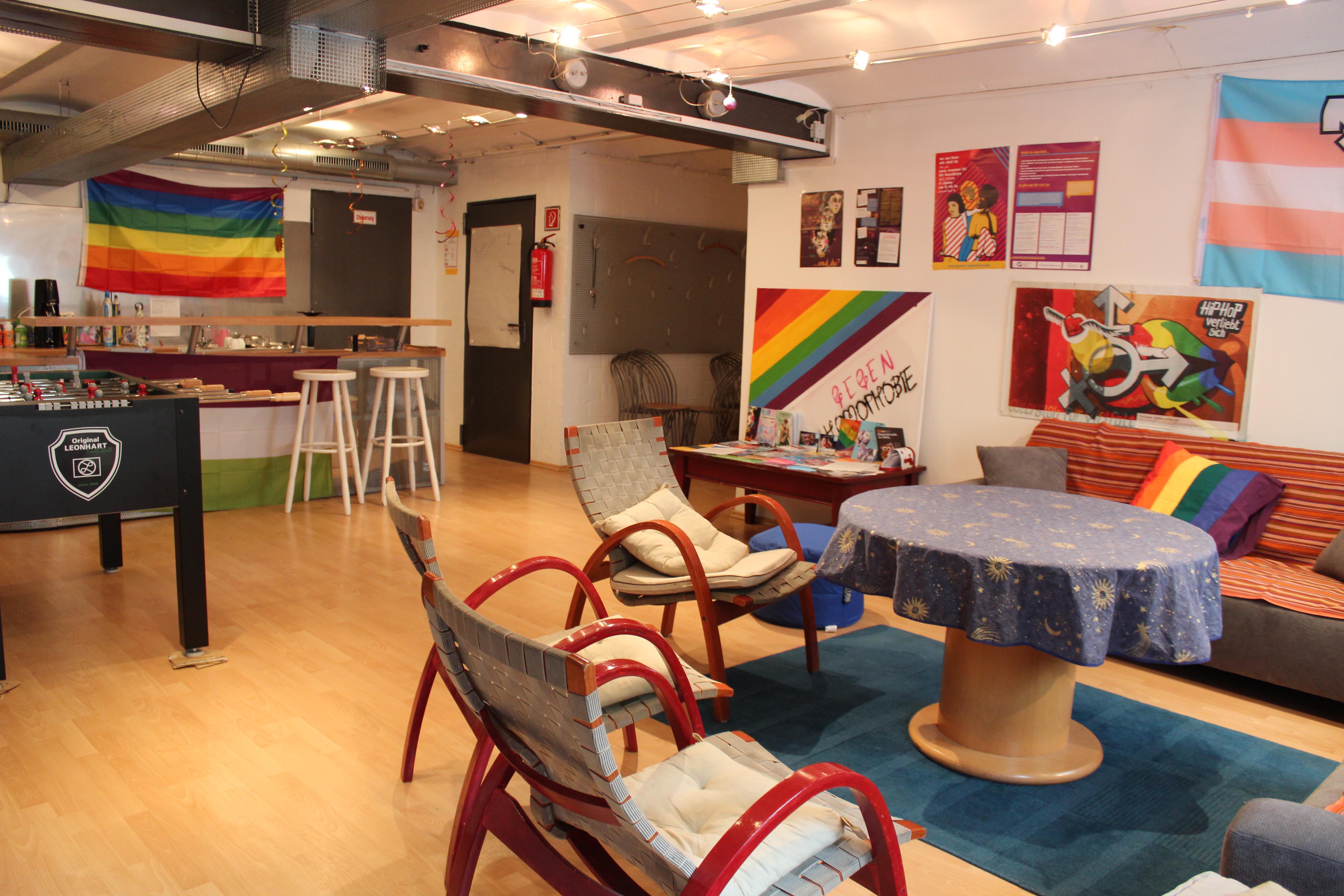 Das Bild zeigt den hellen und freundlichen Gruppenraum. An den Wänden hängen Queere Flagge und es gibt einen Kicker.