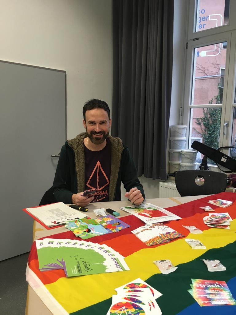 Das Bild zeigt Alex (kurze haare, Bart) an einem Tisch voller Flyer