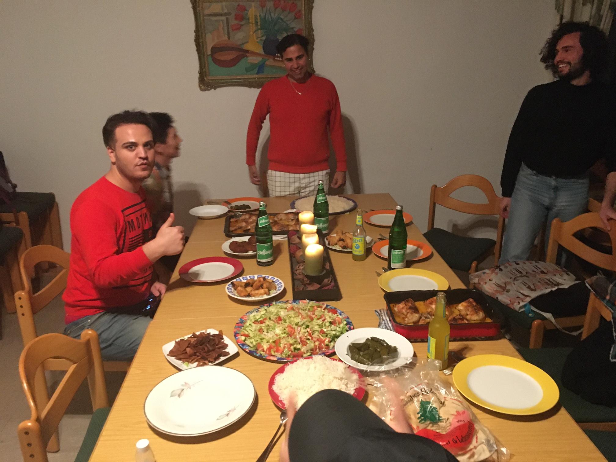 Das Bild zeigt mehrere Personen am Tisch beim Essen