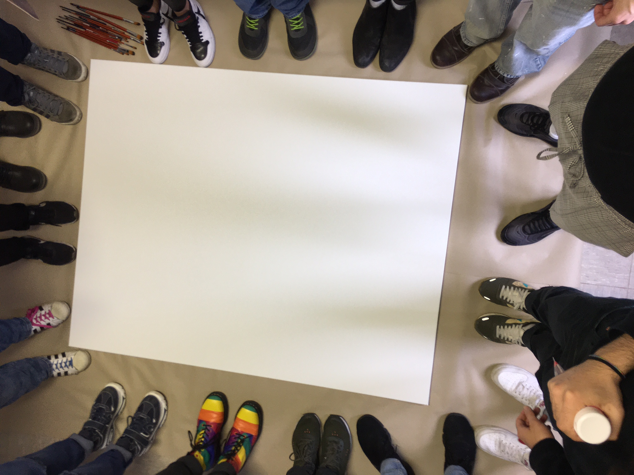 Das Bild zeigt ganz viele Füße die um ein leeres Plakat stehen