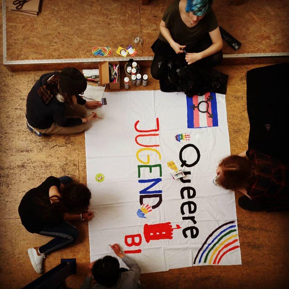 Das Bild zeigt fünf Jugendliche die ein Plakat bemalen auf dem Queere Jugend steht