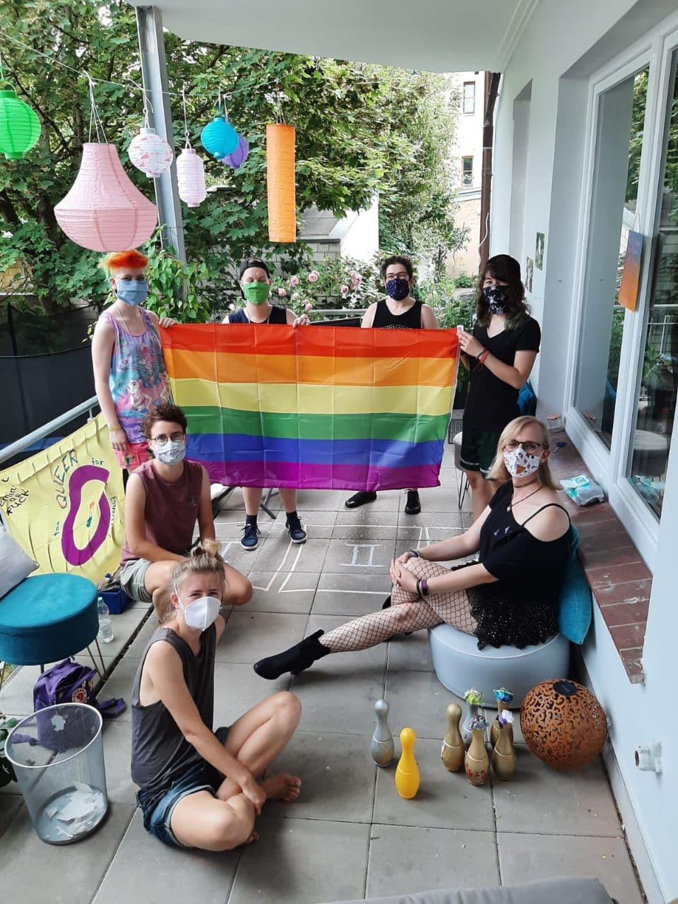 Auf dem Bild sieht man mehrere Jugendliche mit Masken die eine Regenbogenflagge halten