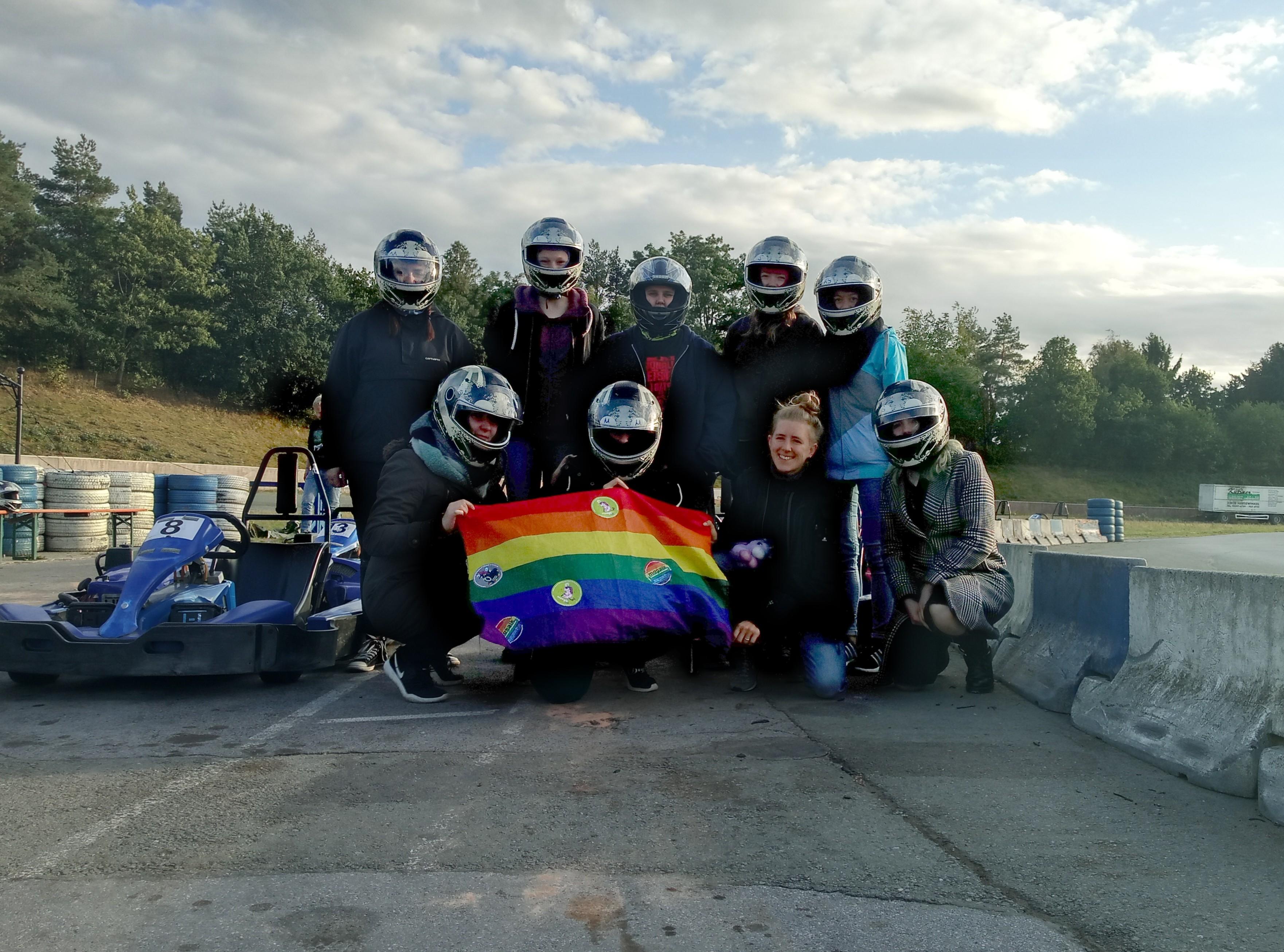 Das Bild zeigt neun Jugendliche. Acht tragen dabei einen Helm. Neben ihnen steht ein Go-Kart und sie halten eine Regenbogenflagge in der Hand