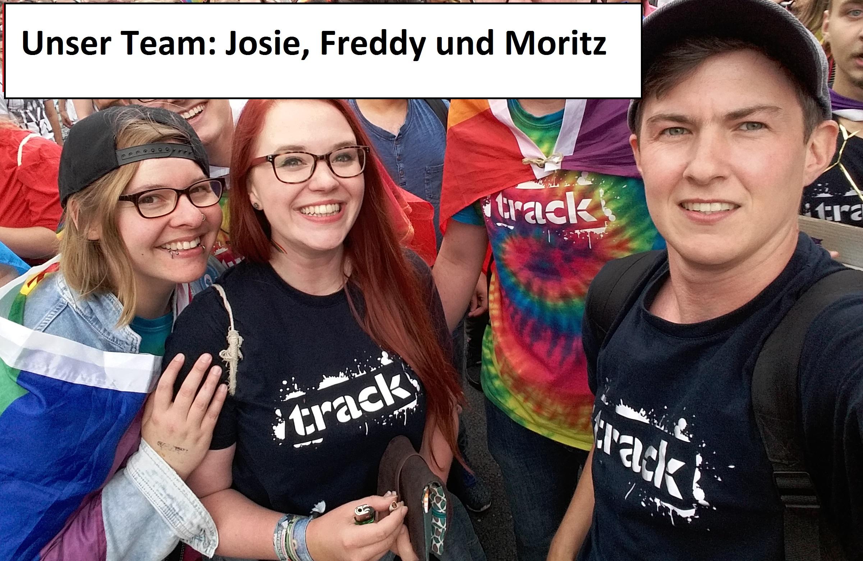 Das Bild zeigt 3 Menschen, die nebeneinander stehen und fröhlich aussehen. Die Menschen sind die Mitarbeitenden des Track.