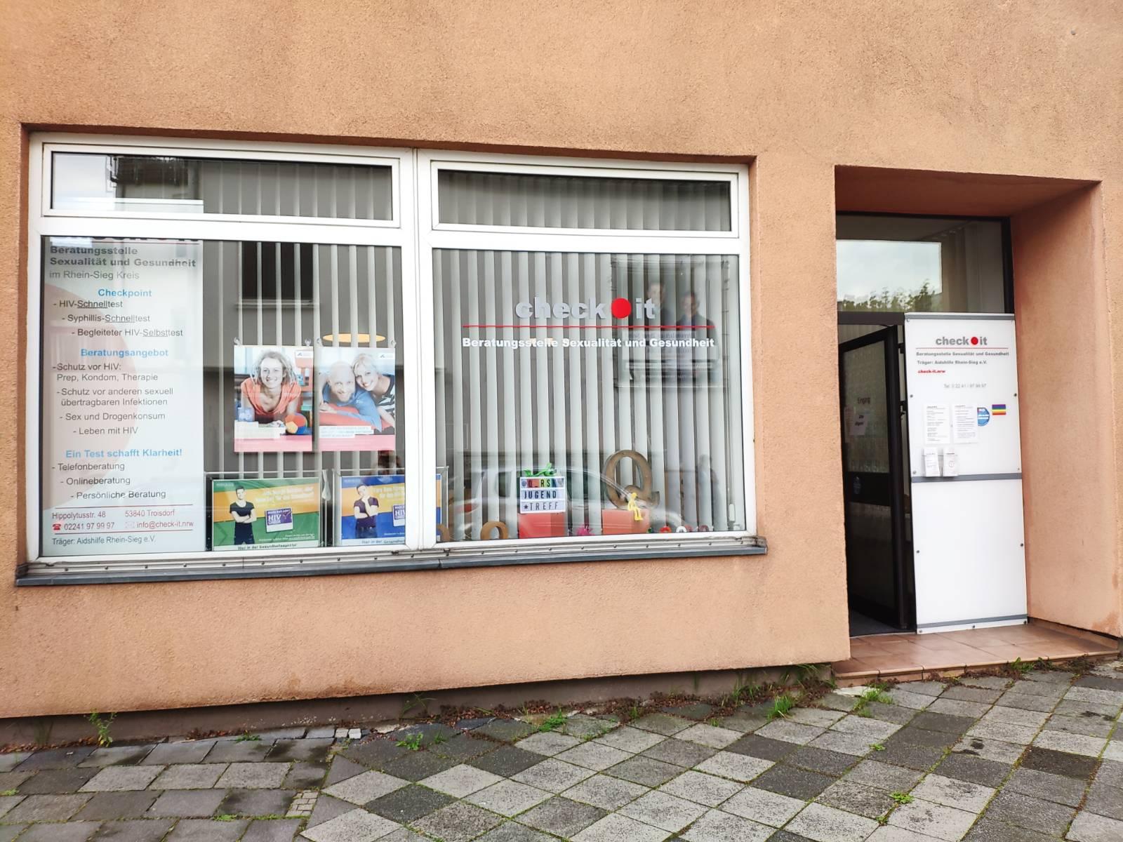 Das Bild zeigt eine Fensterfront mit der Aufschrift: Check it - Beratungsstelle Sexualität und Gesundheit