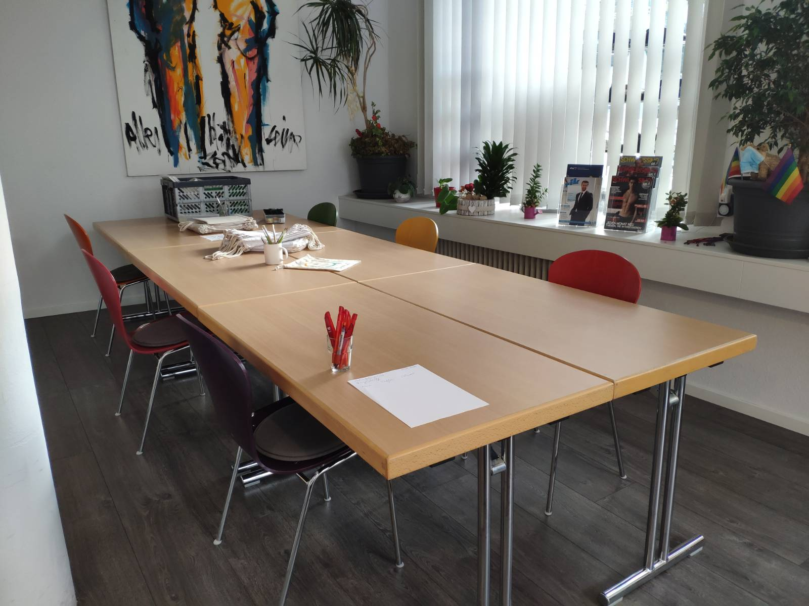 Das Bild zeigt einen großen Tisch mit vielen Stühlen drumherum