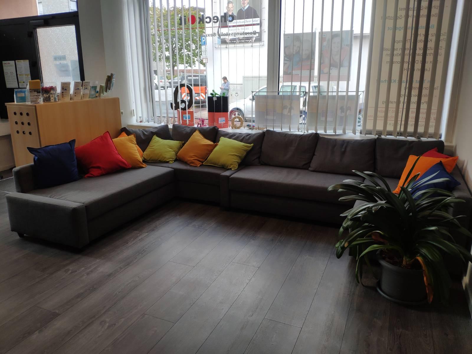 Das Bild zeigt eine graue Sofa-Ecke mit bunten Kissen drauf die vor einem großen Fenster steht