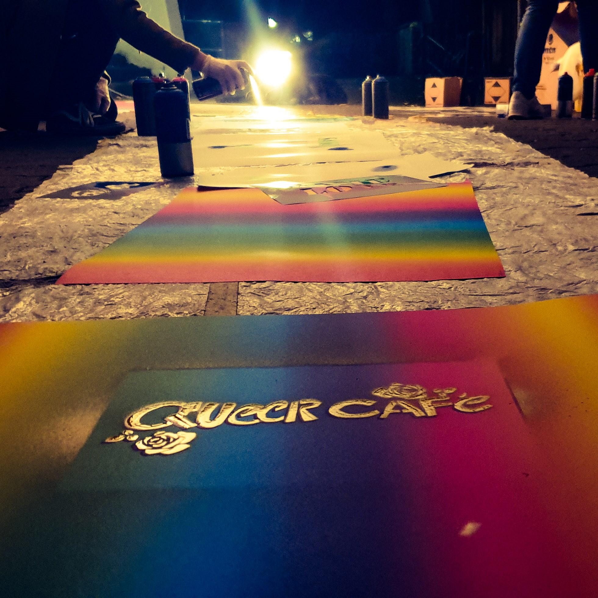 Das Bild zeigt im Vordergrund ein Plakat auf dem Queer Cafe steht im Hintergrund sieht man wie Menschen Plakate besprühen