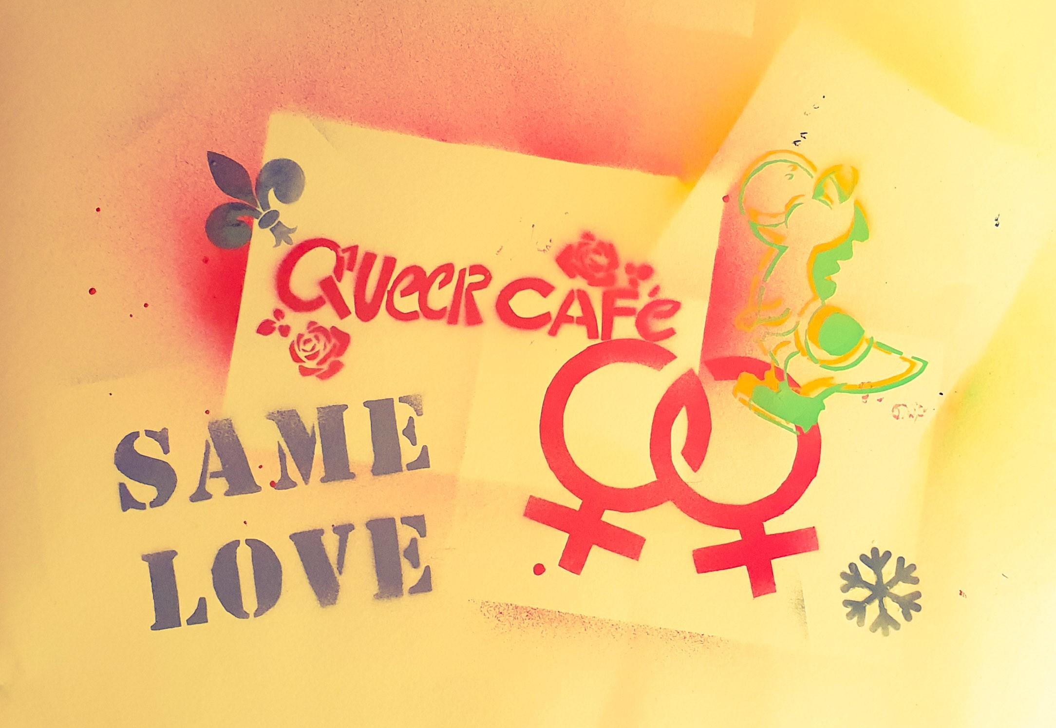 """Das Bild Zeigt ein gesprühtes Bild auf dem zwei ineinander verschlungene Zeichen für """"weiblich"""" zu sehen sind. Daneben steht """"same Love"""" darüber """"Queer Cafe"""""""