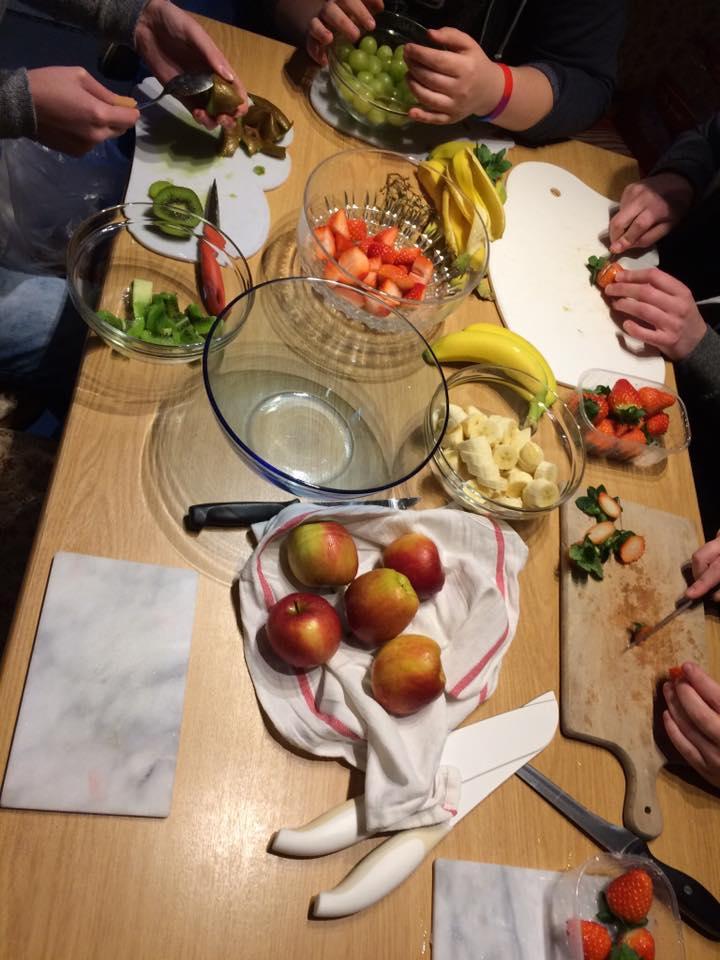 Das Bild zeigt einen Tisch mit einer Vielzahl von verschiedenen Obst Sorten und Menschen die es klein schneiden