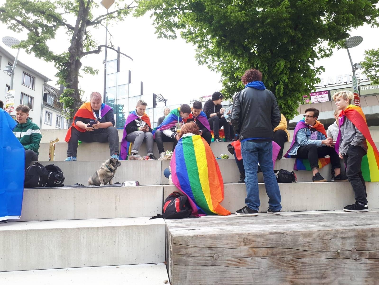 Das Bild zeigt eine Treppe auf der Menschen mit Regenbogenflaggen sitzen