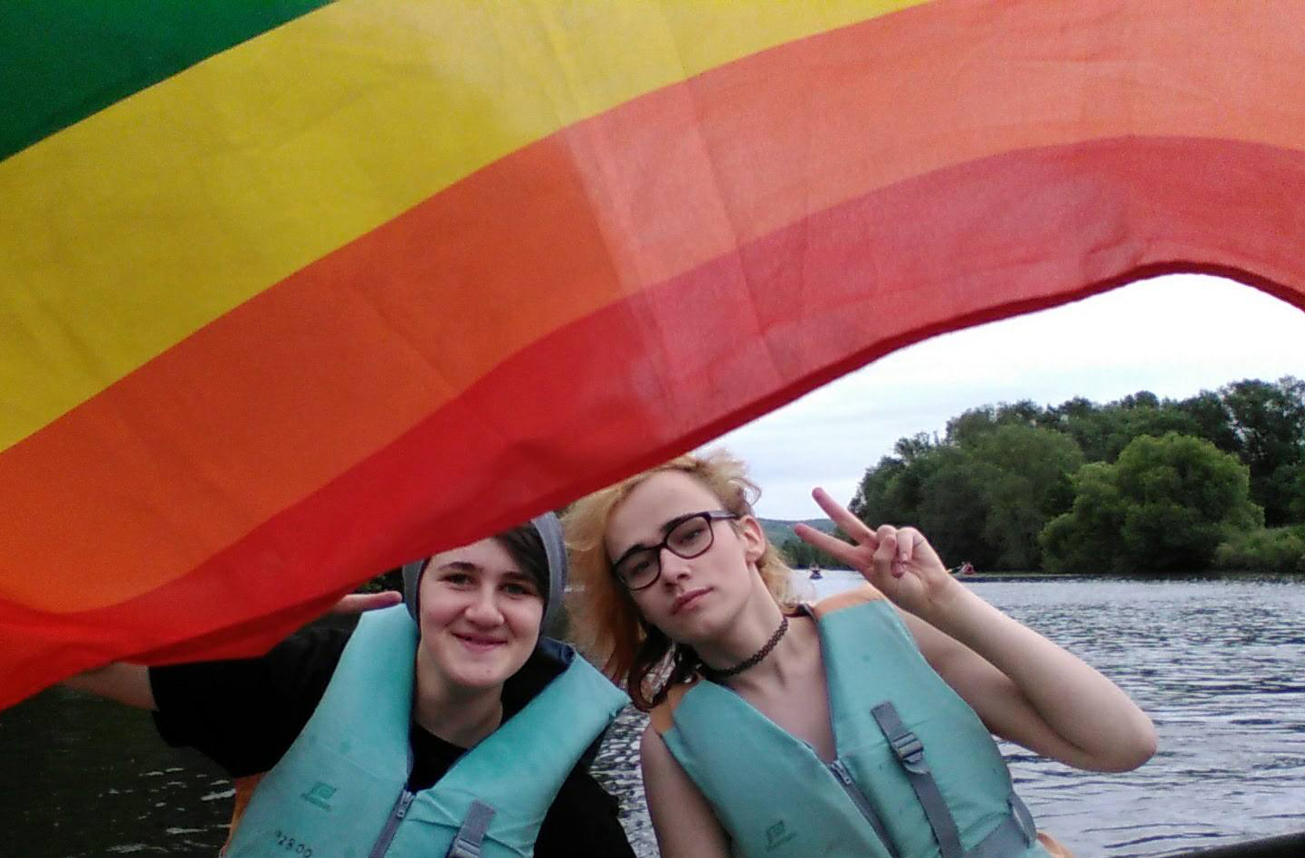 Das Bild zeigt zwei Menschen in einem Boot auf dem Wasser mit einer wehenden Regenbogen Flagge