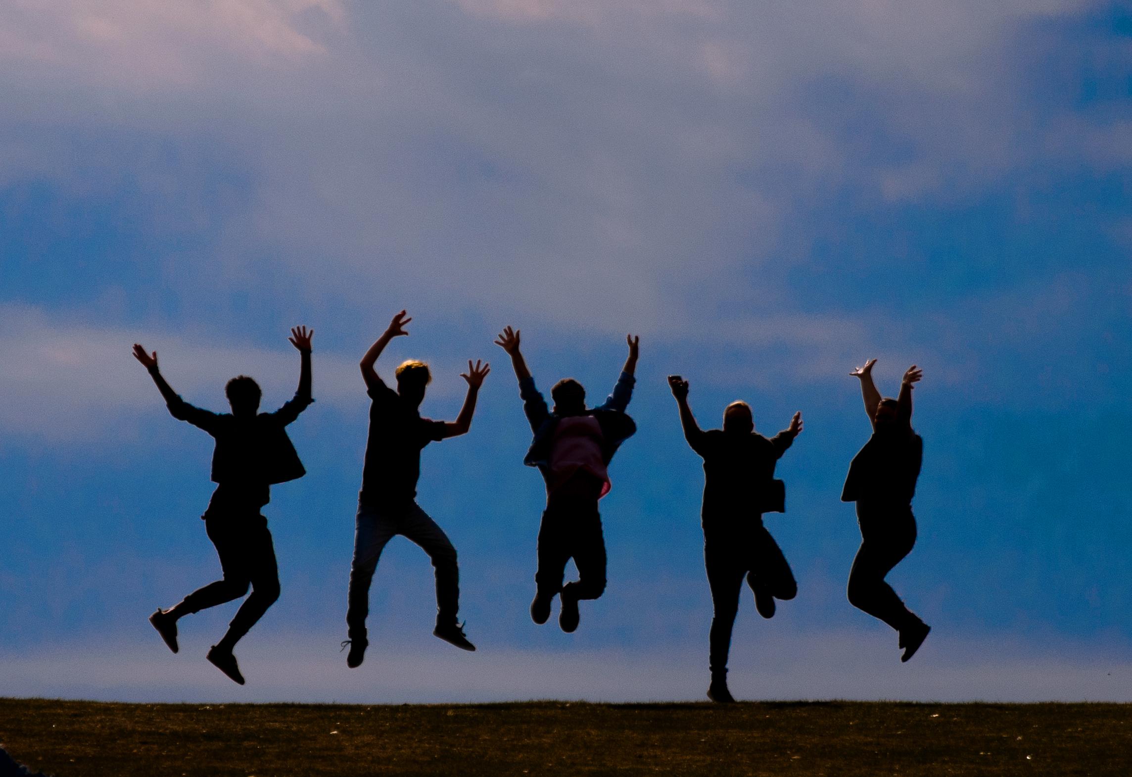 Das Bild zeigt fünf Personen, von denen man nur die Umrisse erkennen kann, wie sie in die Luft springen. Im Hintergrund sieht man den Himmel mit einigen Wolken.