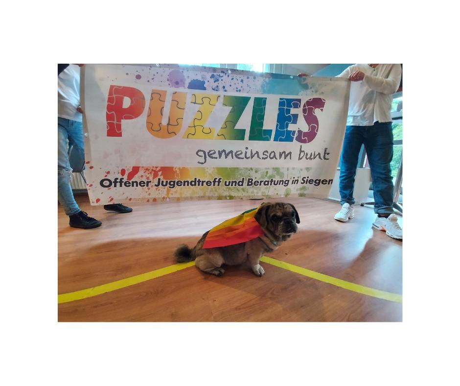 """Das Bild zeigt eine Flagge mit bunten Farbkleksen auf der """"Puzzles - gemeinsam bunt"""" steht. Vor der Flagge sitzt ein kleiner Mops mit Regenbogen Cape."""