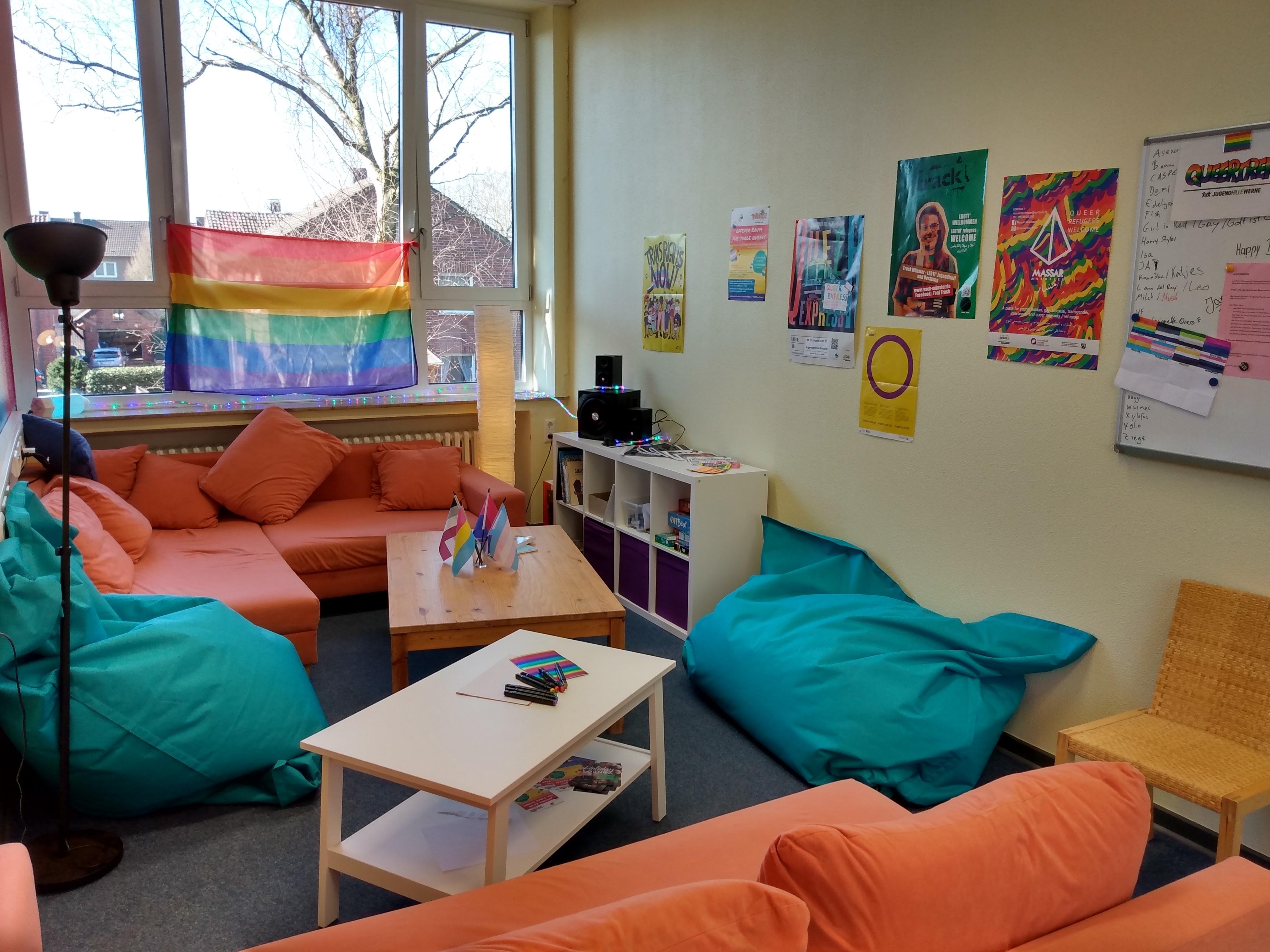 Das Bild zeigt eine terracotta farbende Couch vor der ein Tisch mit vielen verschiedenen Flyern steht