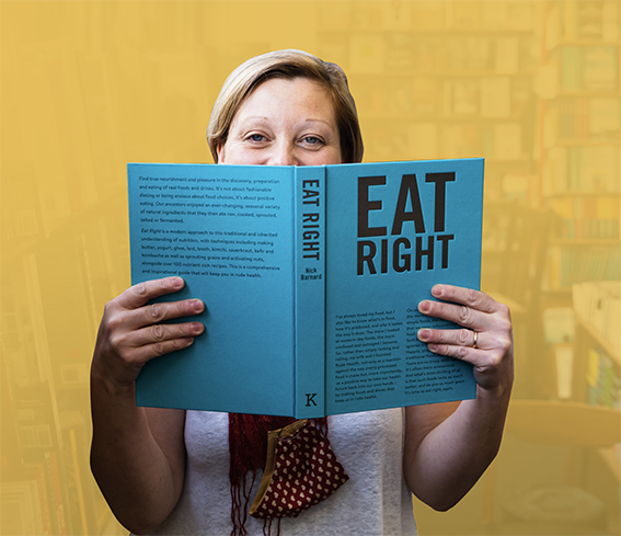 Claire holding up book of how to eat well.