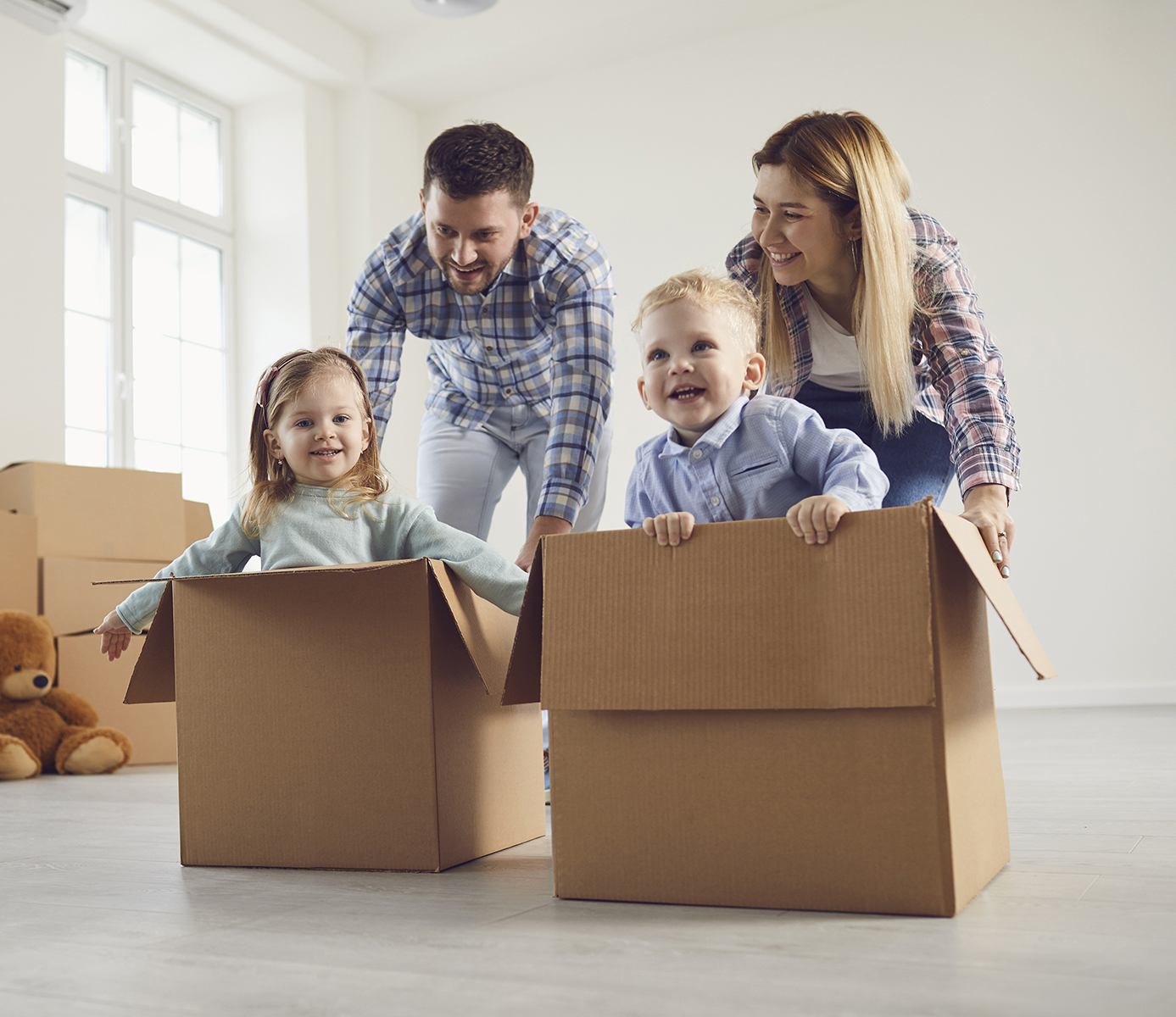 Image of 2 small children being pushed in cardboard boxes by parents