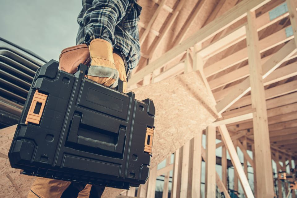 Worker on construction site carrying toolbox