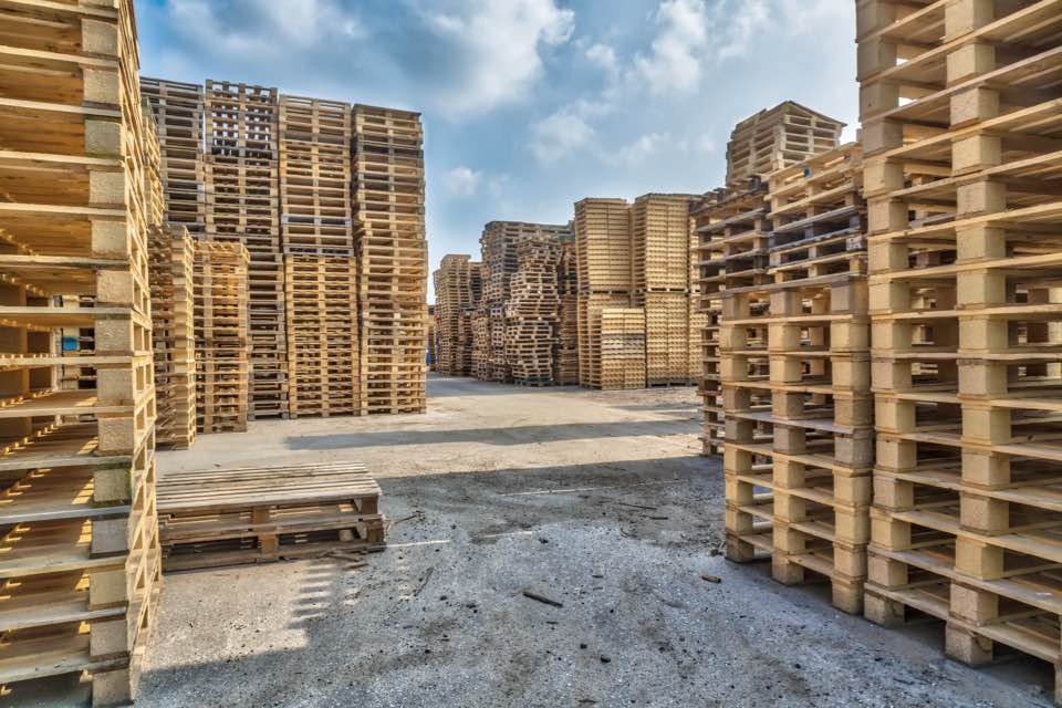 Large amount of wooden pallets stacked in outside yard