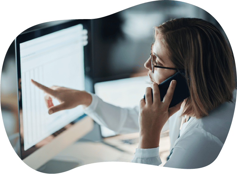 A woman pointing at her computer while talking on the phone