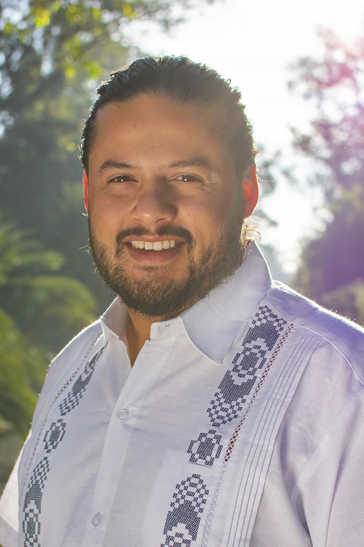 Retrato de Sebastián Ramírez con guayabera en fondo de plantas