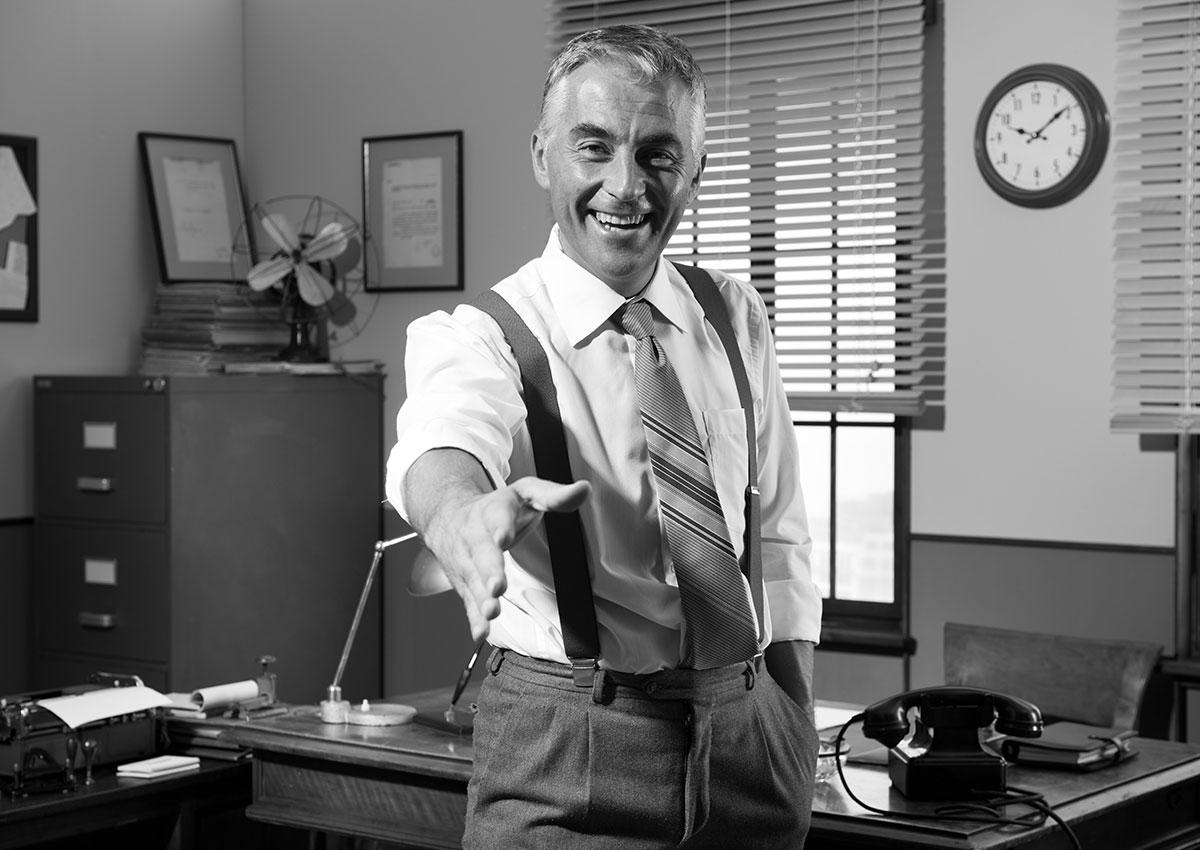 Photo vintage d'un directeur dans son bureau tendant la main