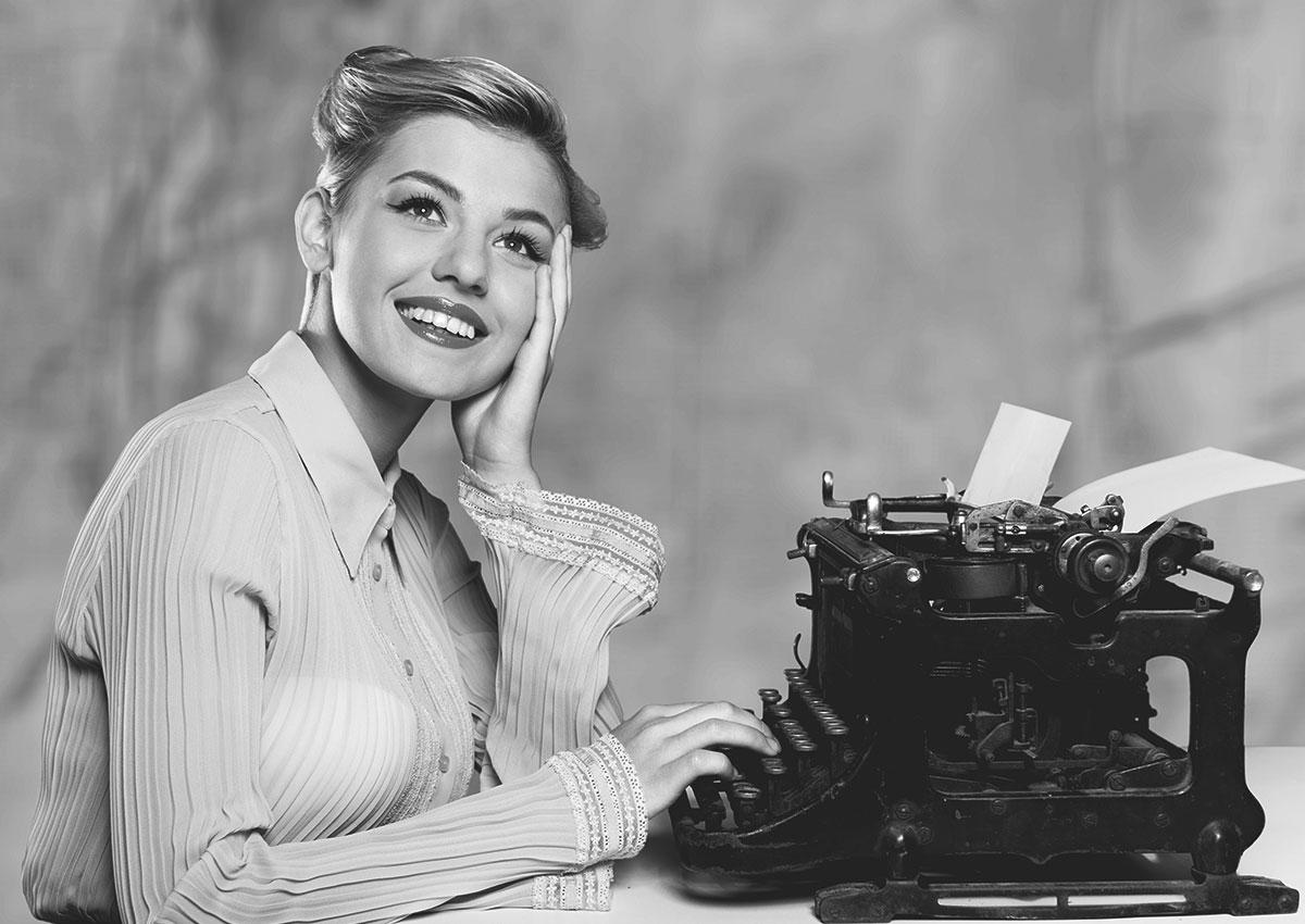 Photo vintage femme pensive devant une machine à écrire