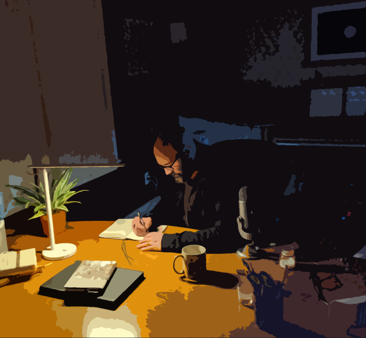 Photo of Anthony Pica writing at his desk at night