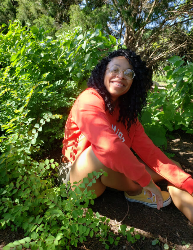 Nadia Johnson sitting in a coral sweater surrounded by leaves