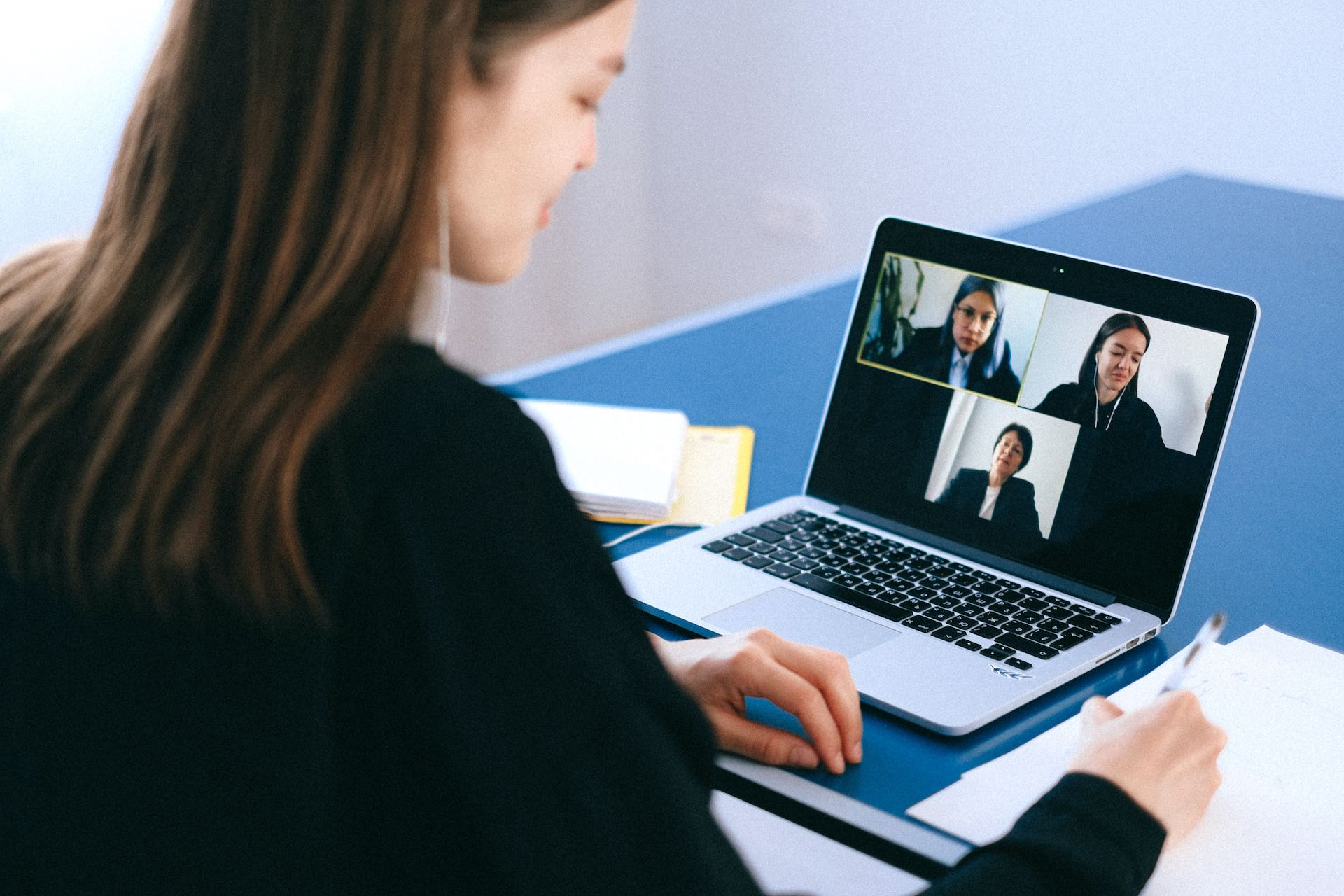A young woman interviewing in a home office on a Zoom call with three managers.