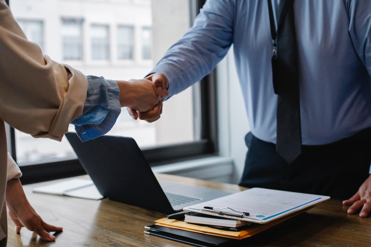 Two people shake hands across a desk after a successful interview. The setting is corporate and in a tall buildiing.