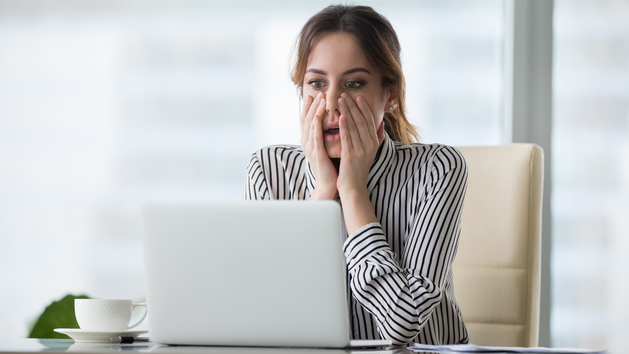 A woman is sitting at her desk looking at her laptop, her hands are covering her mouth as she looks shocked.