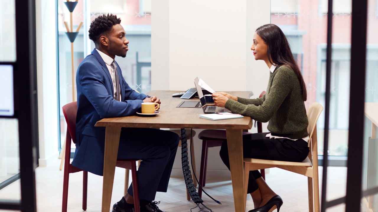 A man and a woman are sitting opposite each other at a small table. She is holding a copy of his CV and is interviewing him for a job