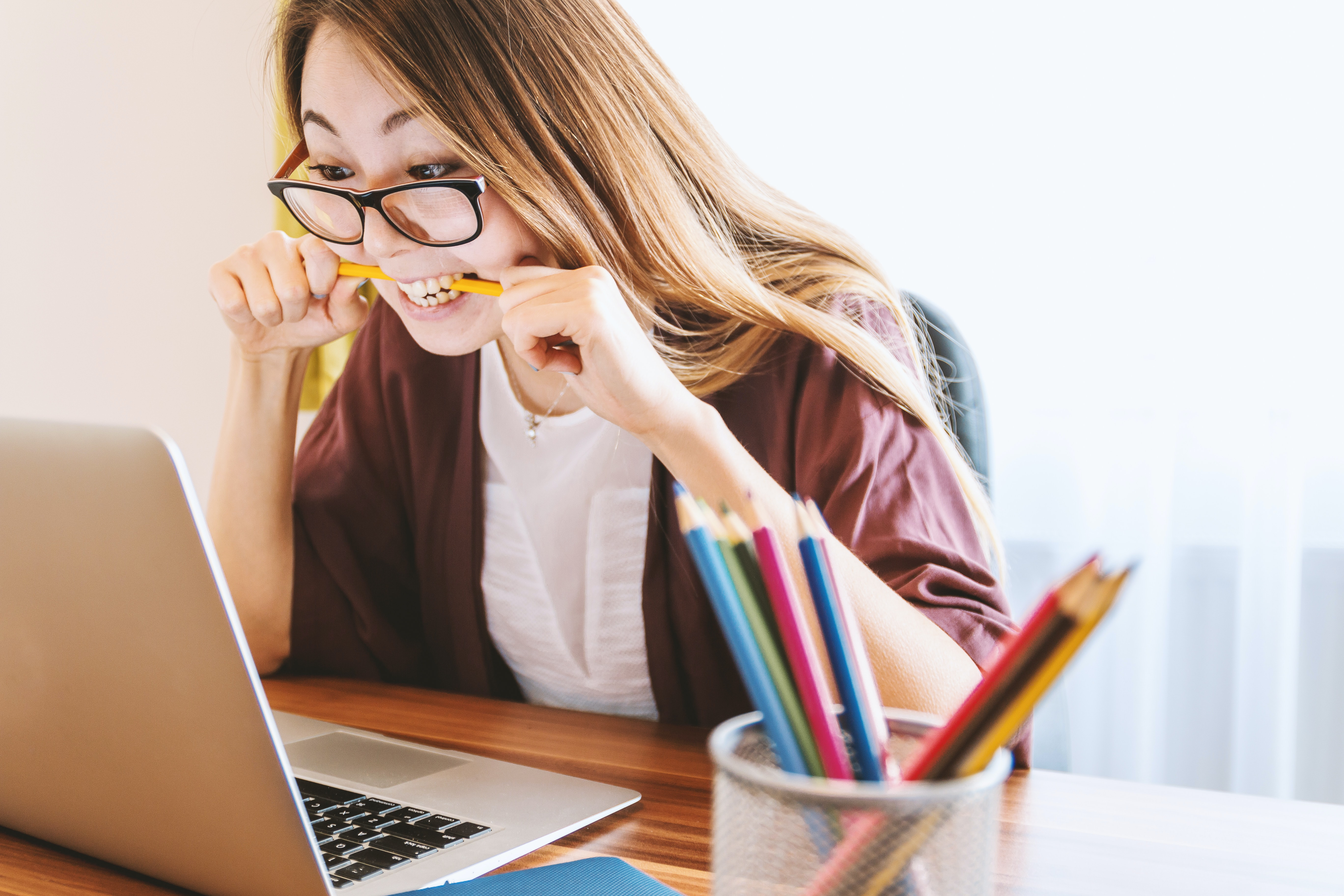A young lady is looking at her laptop screen whilst sitting at her desk, she is clearly frustrated and is biting on a pencil. On her desk is a pot full of coloured pencils.