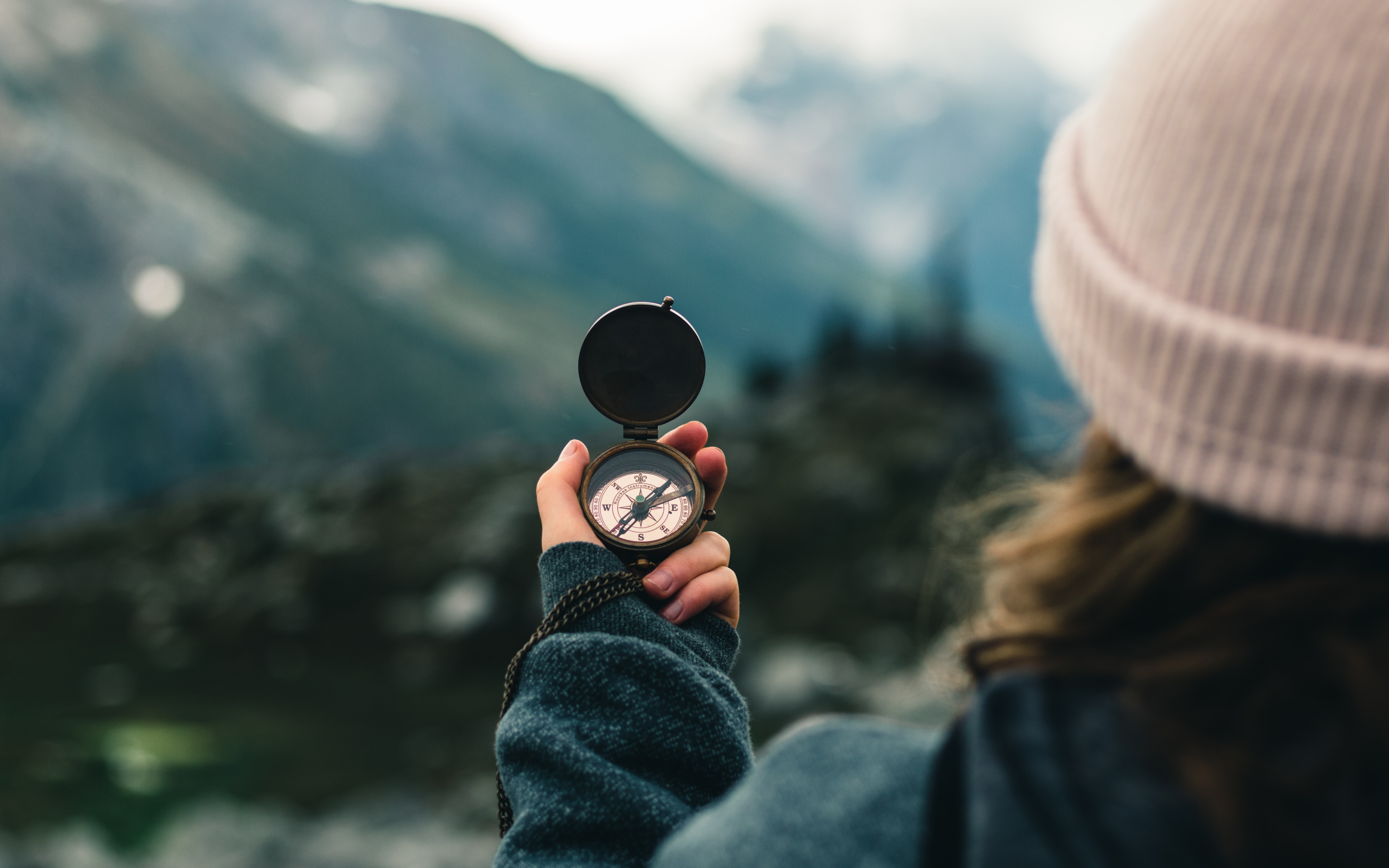 A lady in a pink hat is standing on a mountain. She is looking out at a beautiful view of a mountain range and is holding up a compass.