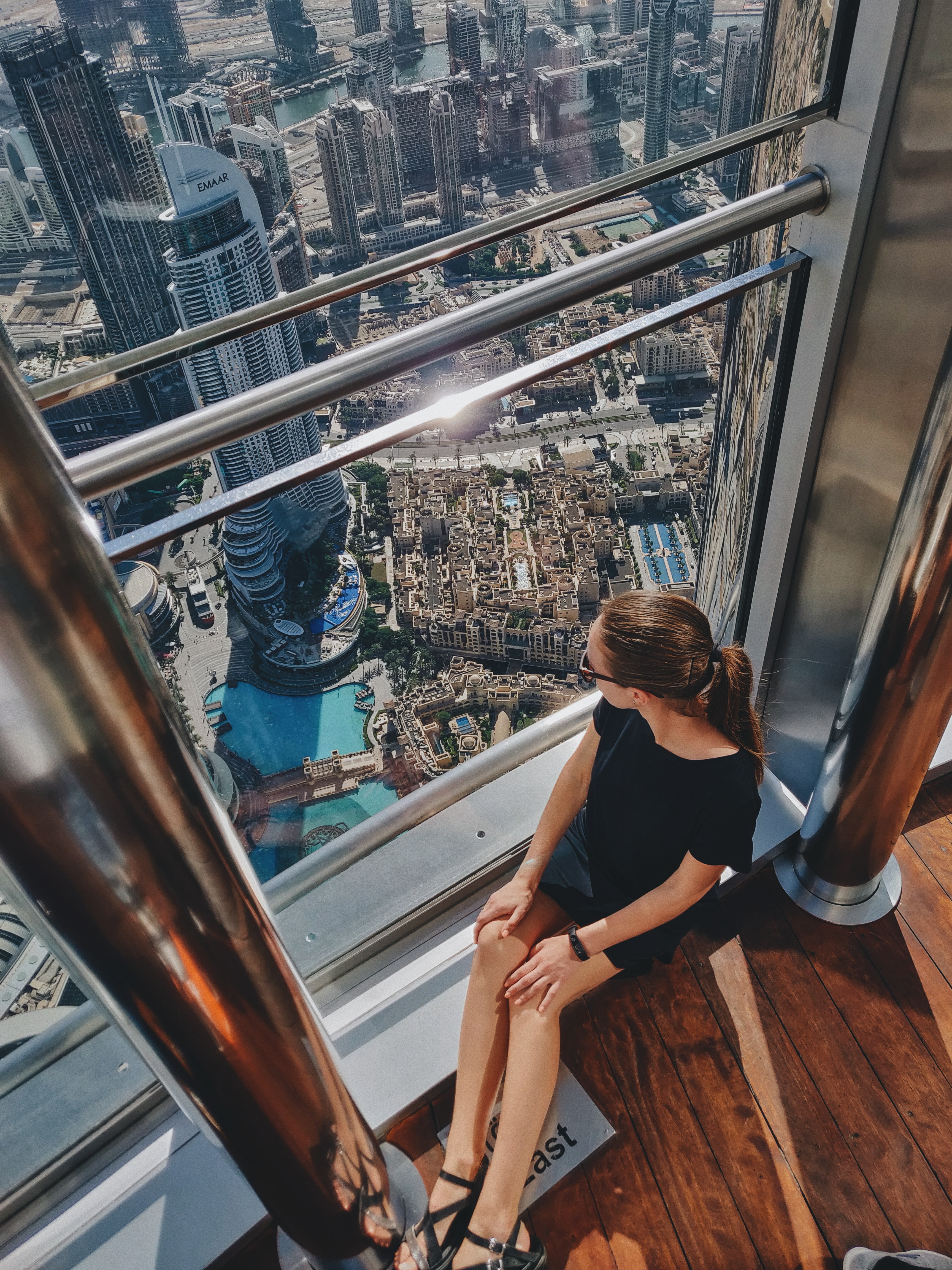 A girl is sitting on the floor at the lookout platform at the top of the Burj Khalifa in Dubai, UAE. She is looking down at the Address Hotel in downtown Dubai