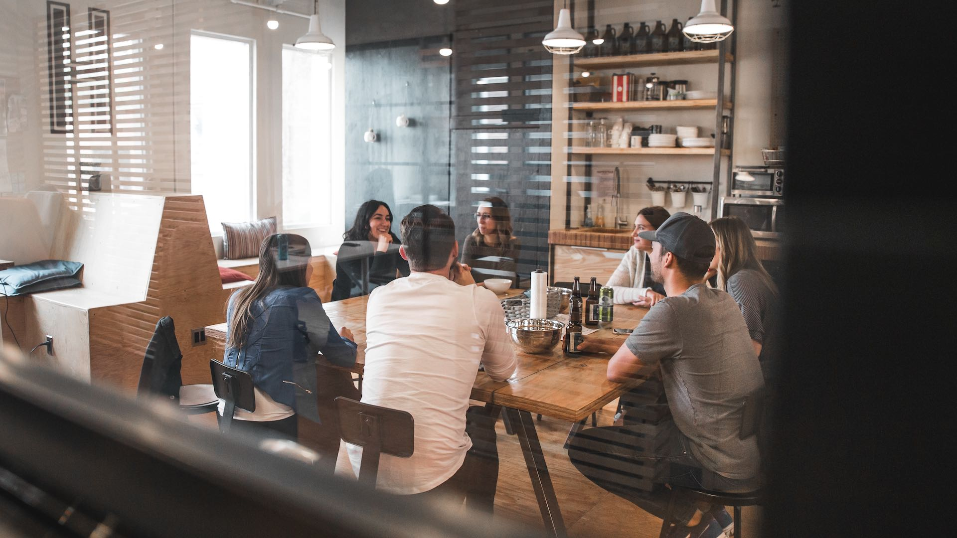 A very relaxed office meeting conducted in a kitchen / eating area. All attendees are sitting around a table, some with drinks, discussing strategy. It has the appearance of being an amazing place to work.