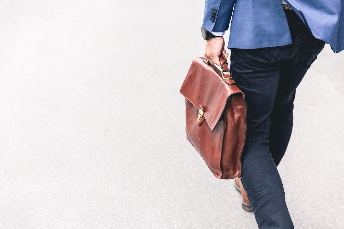 A man dressed in a blazer and jeans, carrying a leather briefcase leaving a successful interview. He was hired using his updated CV / resume from The English Meeting Room.